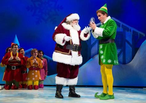 "Image of Santa (Paul C. Vogt) and Buddy (James Moye) in a scene from the Paper Mill Playhouse production of ""Elf."" Michael Coale Grey is the elf far left in red."