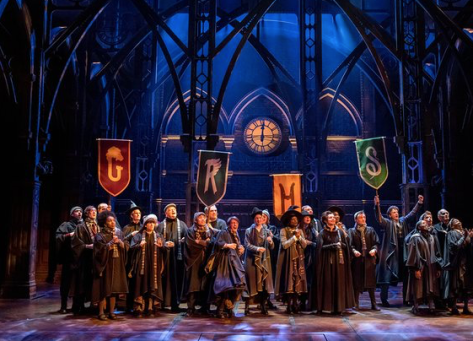 "Pupils at Hogwarts stand under banners of the four school houses in a scene from ""Harry Potter and the Cursed Child."" Photograph Manuel Harlan"